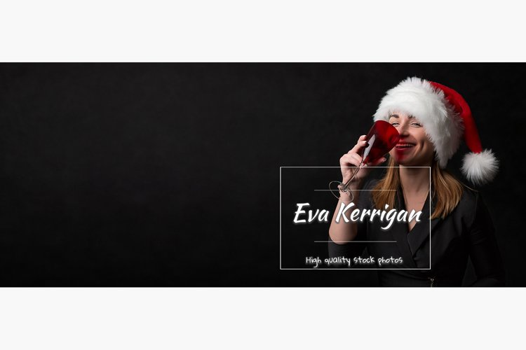 Girl in a santa hat drinks champagne from a red glass. example image 1
