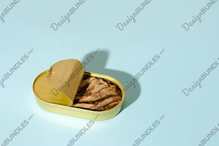 Sprat with oil in an open tin can on blue background