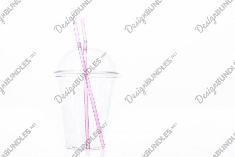 Clear empty plastic cup with dome lid and two pink straws example image 1