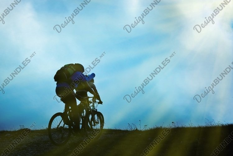 Silhouette of couple on bicycles against clouds and sky example image 1
