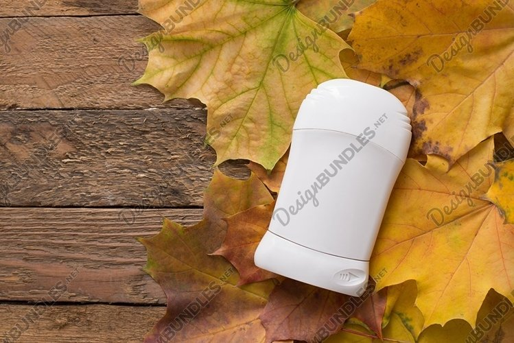 Mock up a bottle of deodorant on yellow autumn maple leaves example image 1