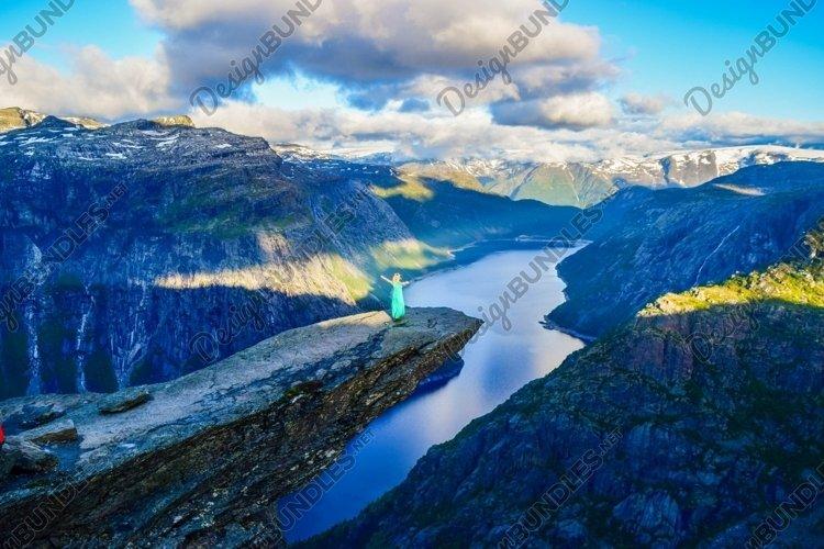 Girl on Trolltunga at sunrise, Norway.