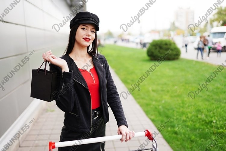 brunette woman shopping bag while standing outdoors example image 1