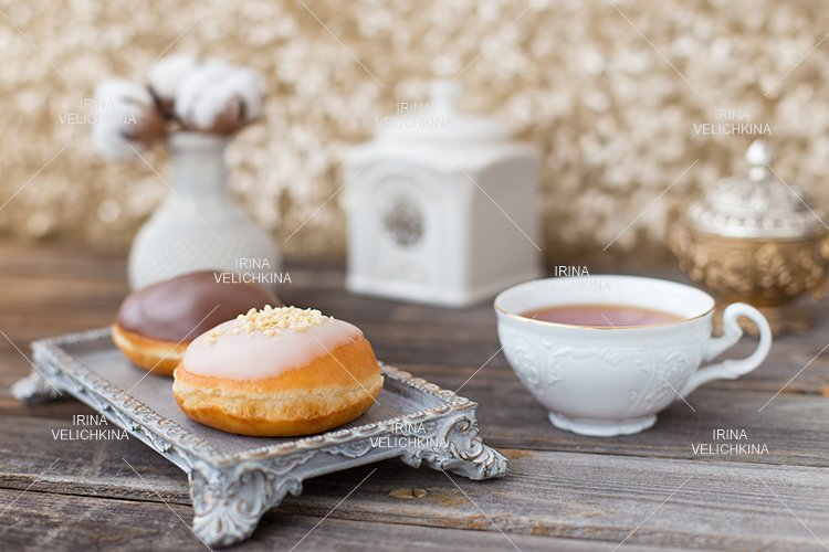 Cup of aristocratic tea with donuts.White milk chocolate,nut