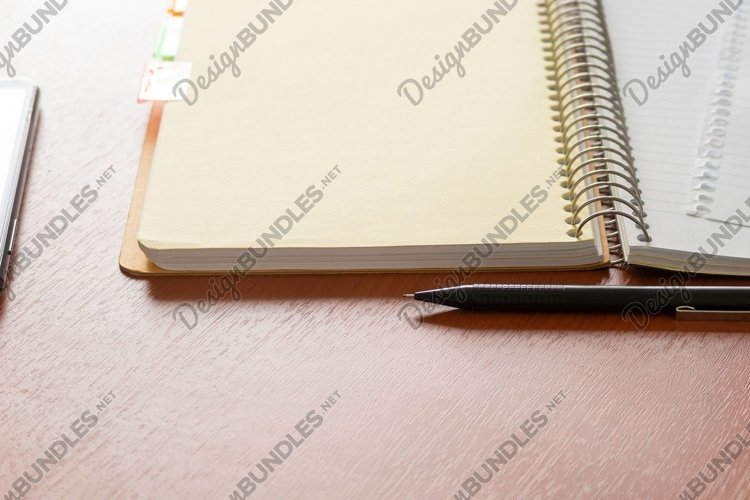 Open notebook, black pencil and mobile phone on table.