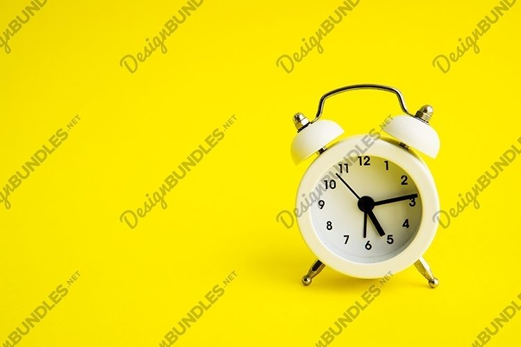 White alarm clock on a yellow background. example image 1