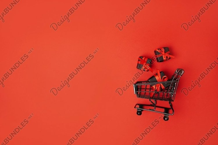 black gift boxes with red bow in shopping cart, black friday