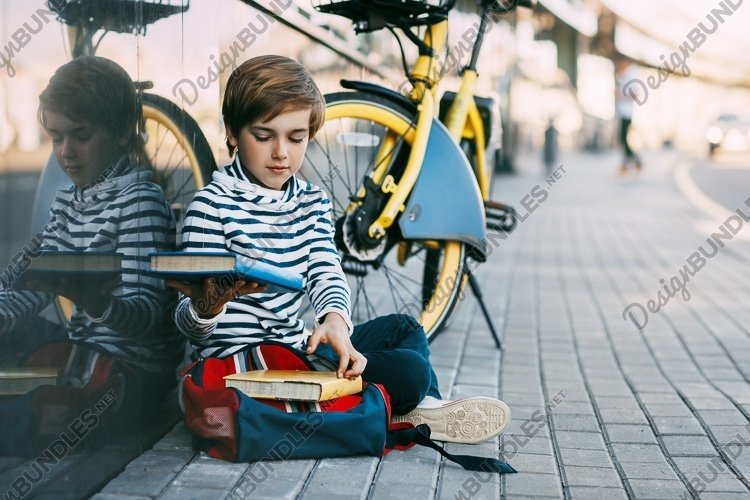 Schoolboy with book and backpack on a bicycle example image 1