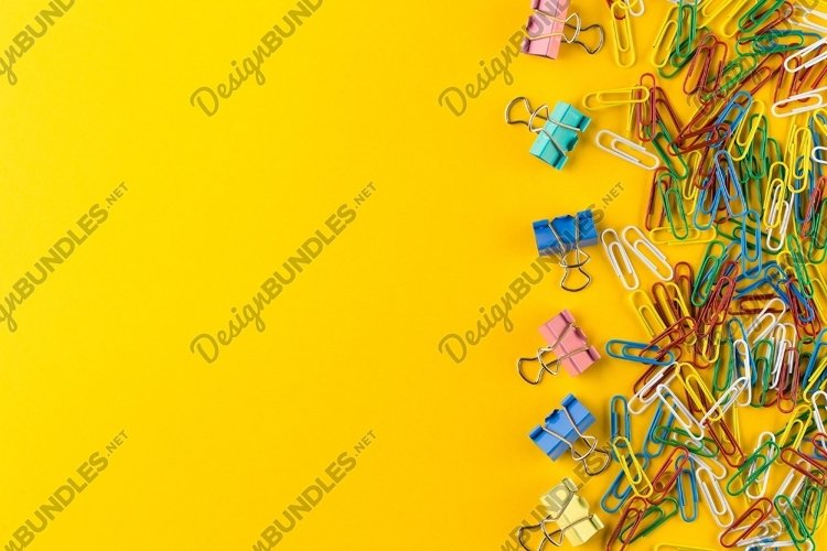 Paper clips and binder clips on yellow background example image 1