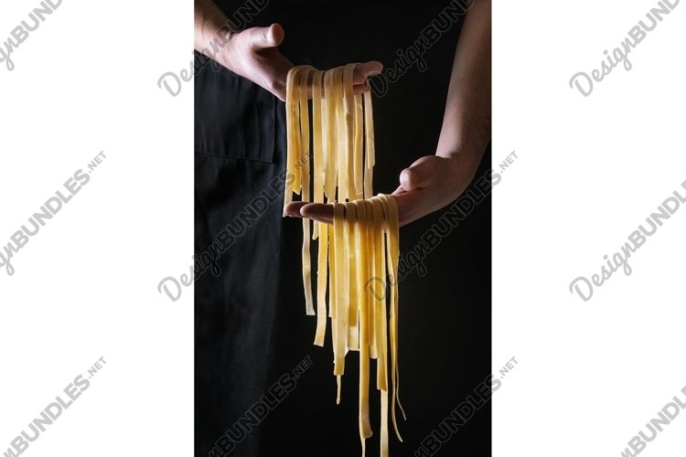 Fresh pasta tagliatelle in man's hands example image 1