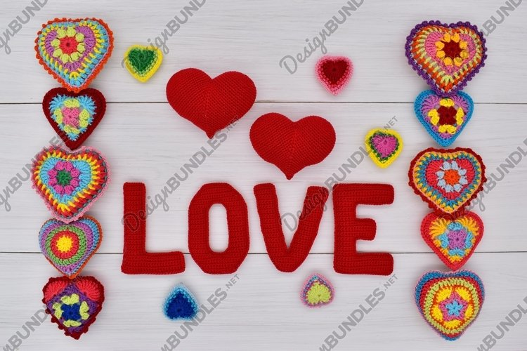 """Knitted hearts and the word """"love"""" on white wooden boards. example image 1"""