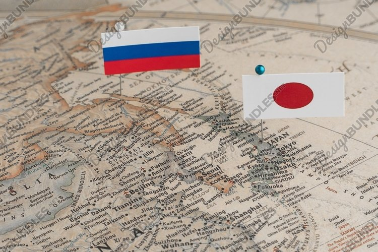 The flags of Russia and Japan on the world map. Politics example image 1