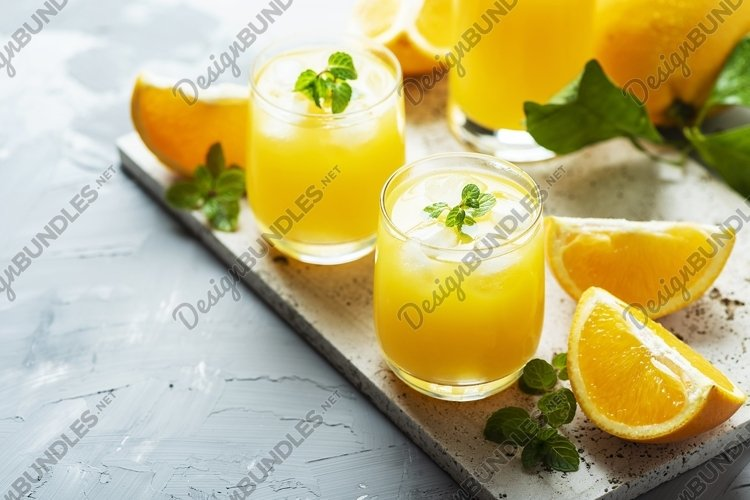 Fresh cold orange juice with green mint and ice example image 1
