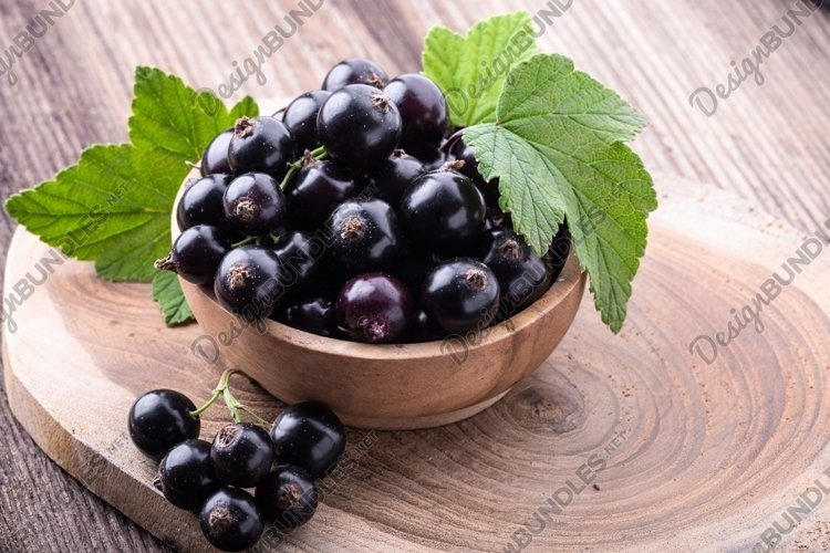 Black currant with leaves on rustic old wooden table. example image 1