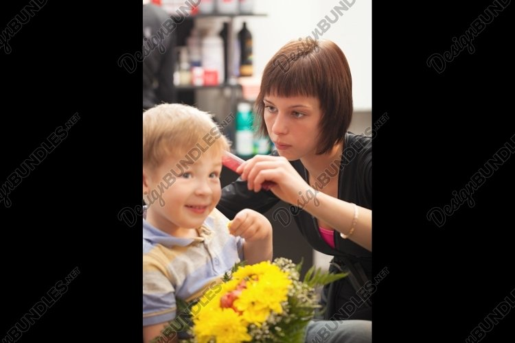 Young boy getting haircut from styist example image 1