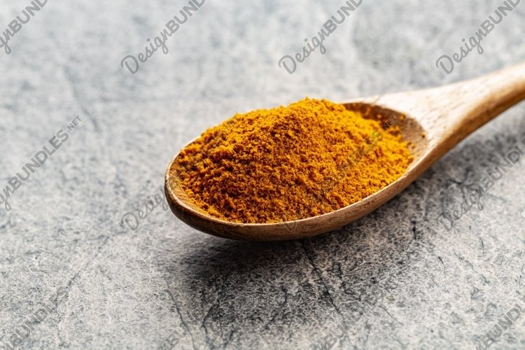 Turmeric powder in wooden spoon on gray example image 1