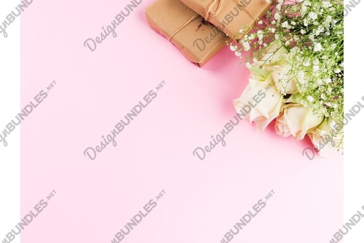 White roses flowers bouquet and gifts on pink
