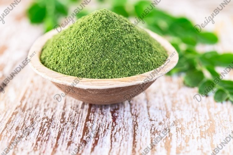 Moringa powder with original fresh leaves on wooden table. example image 1
