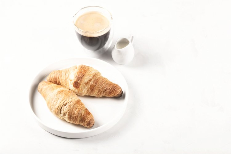 Croissants and coffee in the style of minimalism.