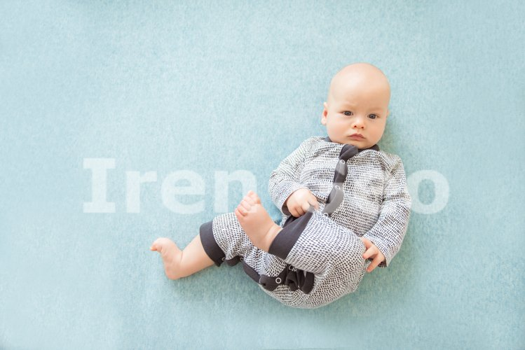 Calm curious baby lying on blue background