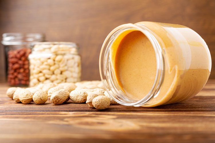 Creamy peanut paste in open glass jar, peanut butter photo