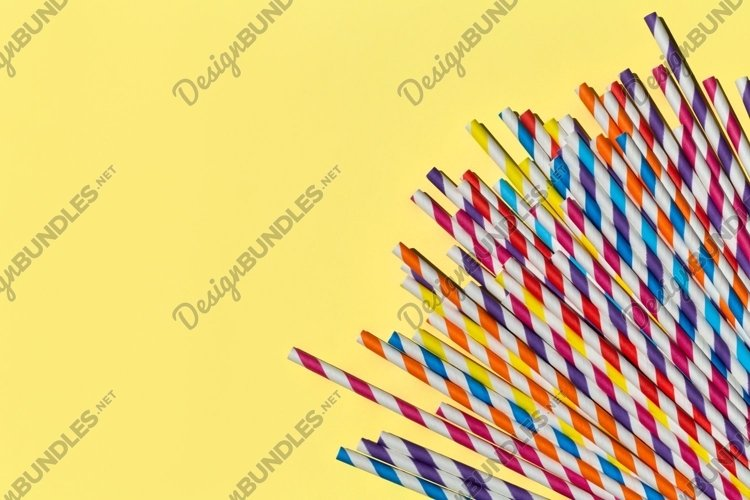 Multi-colored paper straws for party on a bright yellow example image 1