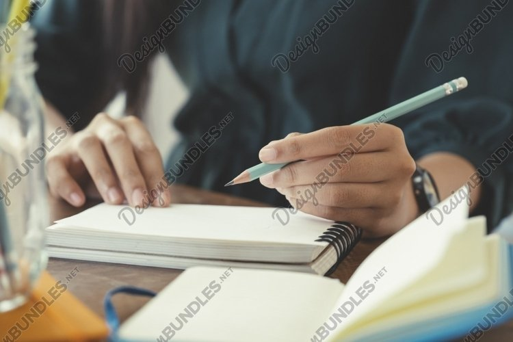 Close up hands with pen writing on notebook. example image 1