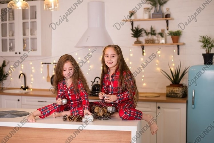 Two little charming girl sisters in same red pajamas example image 1