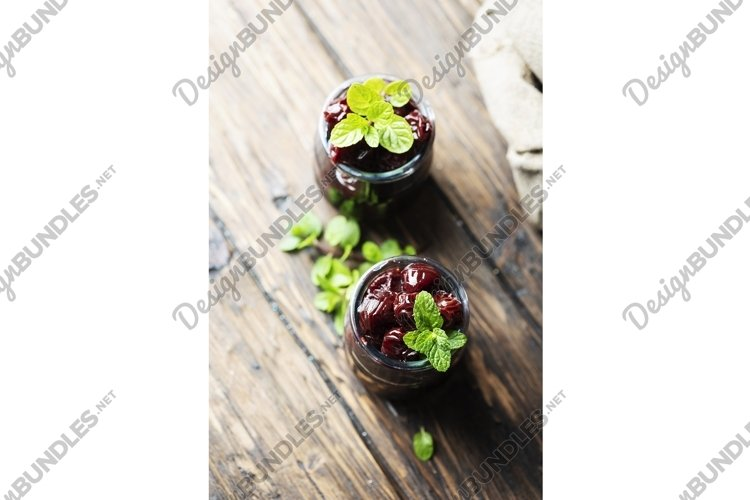 Two jar of homemade cherry preserve on the wooden table example image 1
