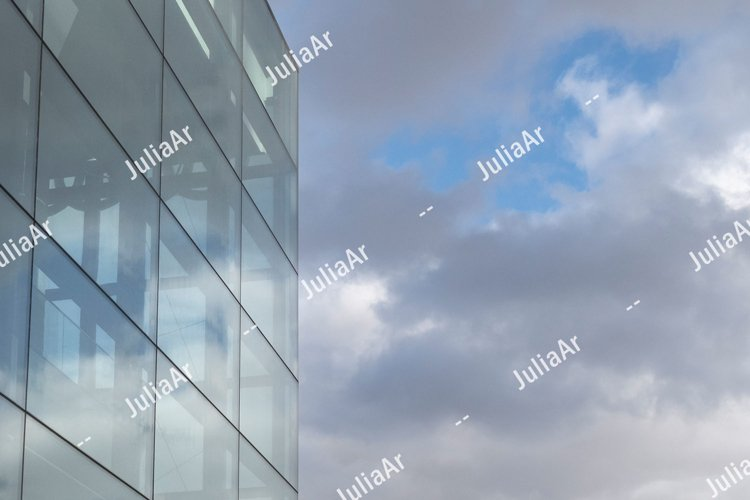 Glass wall against cloudy sky with copy space example image 1