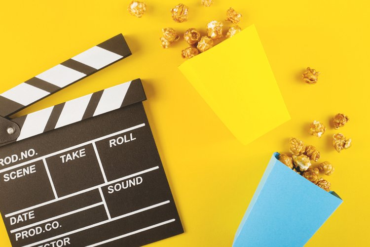 Popcorn and clapperboard on yellow background. Top view example image 1