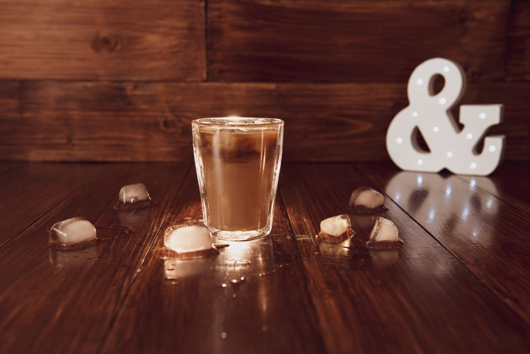 Iced coffee with ice cubes on table