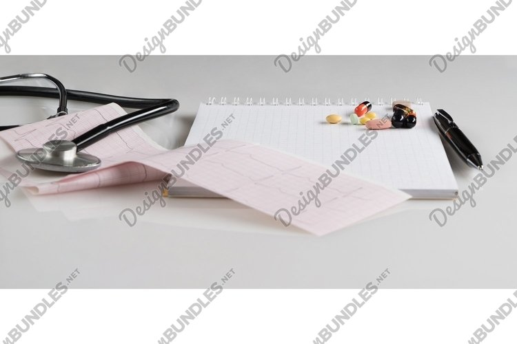 Medical stethoscope with pills and cardiogram on white example image 1