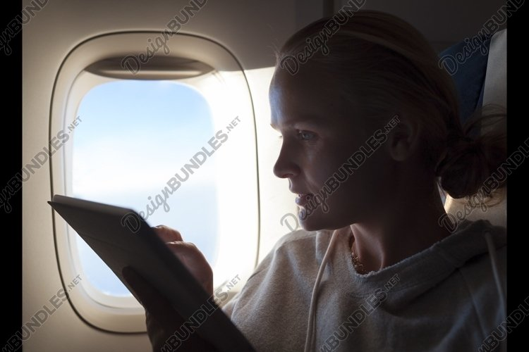 Woman sitting by illuminator in plane with touch pad example image 1