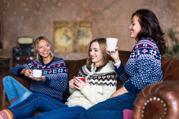 Three happy friends drinking coffee relaxing on the sofa example image 1