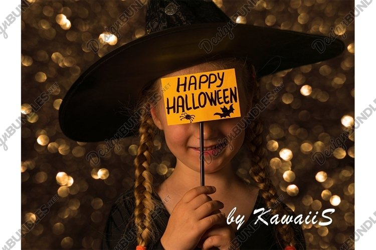 Child in a hat with Happy Halloween greeting card smiling