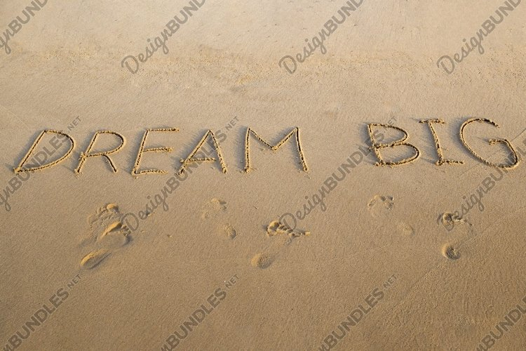 Handwritten DREAM BIG on a sandy sea beach example image 1
