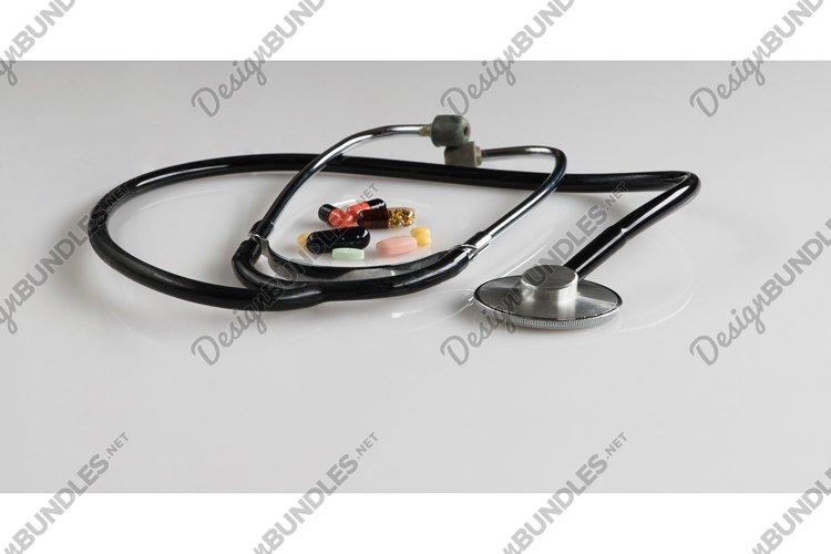 Medical stethoscope with pills on white background, isolated example image 1