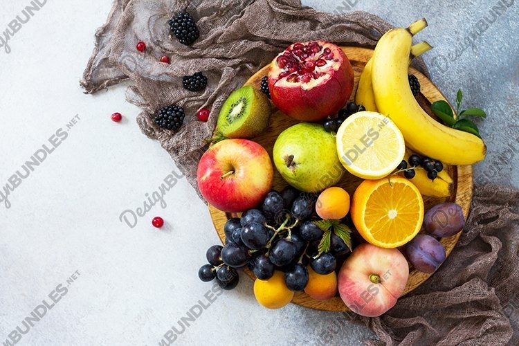 Fruit background. Fresh mixed fruits on a gray stone table.