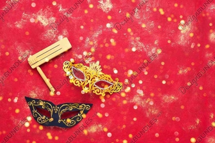 Carnival mask and wooden gragger on bright red background. example image 1