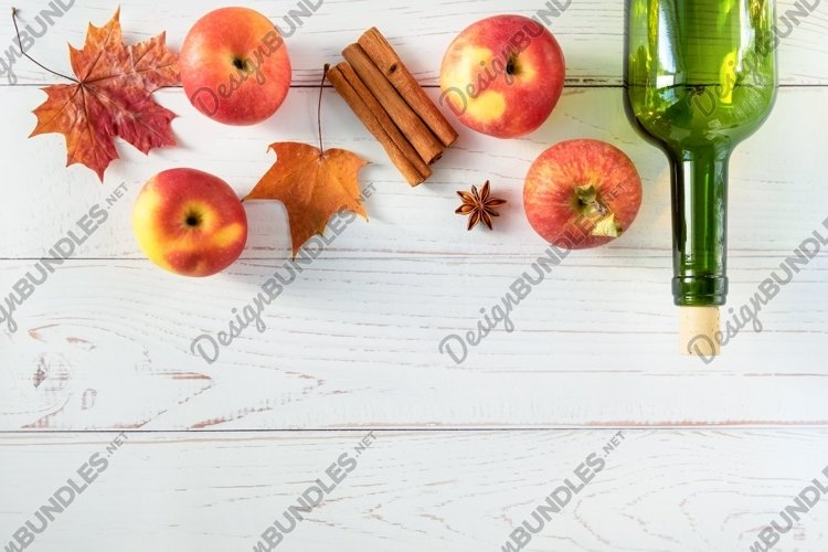 Ripe red apples, spices and a bottle with cider example image 1
