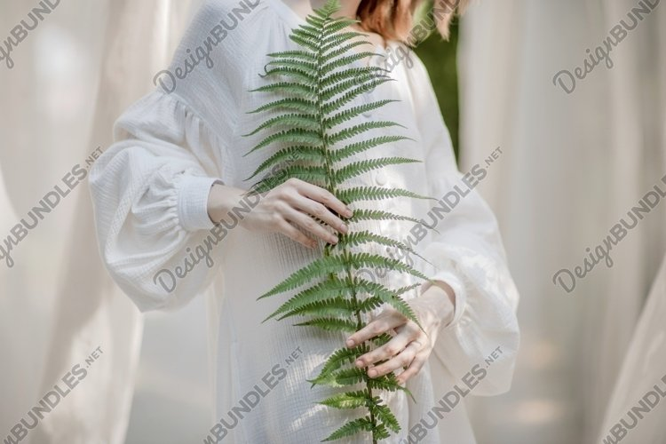 tender girl holding a plant example image 1