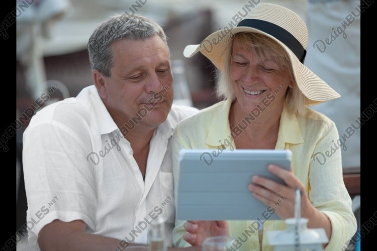 Cheerful mature couple with touch pad outdoor example image 1