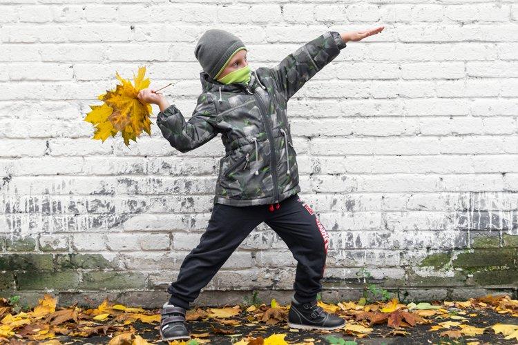 a boy, near a white brick wall