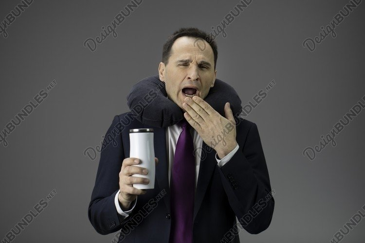 businessman yawns with mug of coffee in hand example image 1