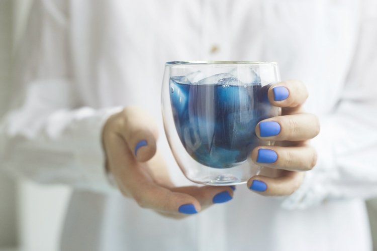 Woman with classic blue manicure holds a glass of matcha.