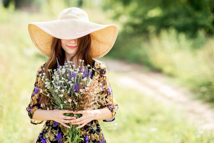 A girl in a hat with a bouquet of wild flowers. Summer photo