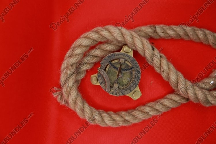 old copper compass and a jute rope on a red background example image 1