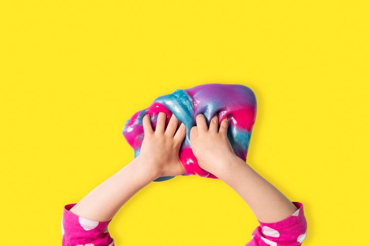 Child hands and colorful pink, blue and purple shiny slime.