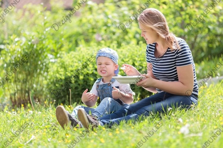 Cute little boy being fed outdoors on the grass example image 1